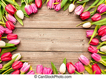Tulips arranged on old wooden background - Frame of fresh...