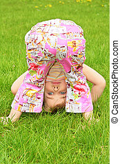 little girl makes gymnastic  on grass