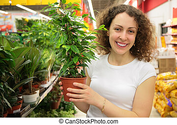 young woman holds pot with plant in shop