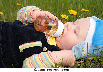 child drinks from a bottle laying in  grass