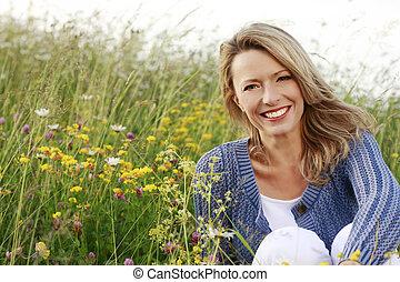 Happy woman in wild flower field - Happy middle aged woman...