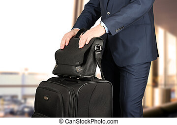 young businessman in a modern stylish suit with luggage in -...