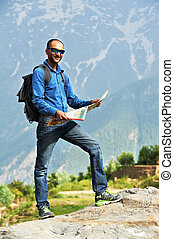 Tourist guide with map in mountains