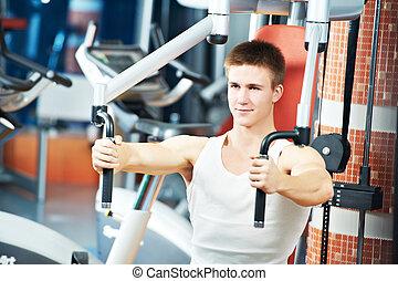 man at chest pectoral exercises machine