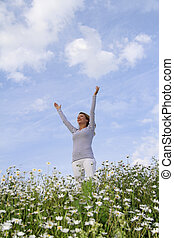 Woman with stretched arms in flower field - Happy woman with...