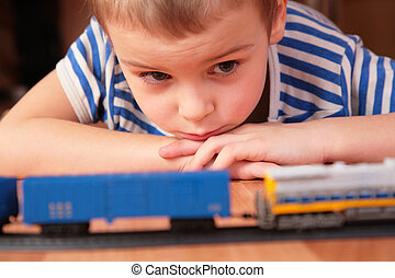 Boy looks at toy railroad