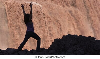 Yoga at Grand Falls Arizona - a woman silhouetted practicing...