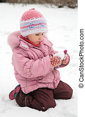 little girl play with snow in winter