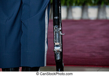 Military rifle of blue soldier standing
