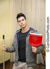 Handsome Young Man Holding Dust Pan and a Broom - Young...