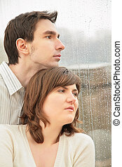 boy with the girl against  background of  wet window