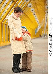son embraces mother on footbridge