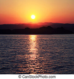 Sunset over a greek island in the Mediterranean sea -...