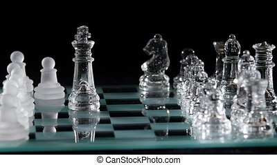 Glassy chess is placed on black background. Slow motion -...
