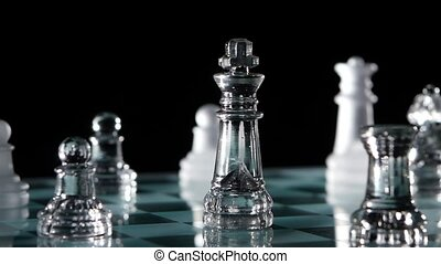 Close up, glass chess pieces over black background. Slow motion