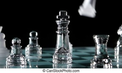 Fight chess pieces on chessboard. Black background. Slow...