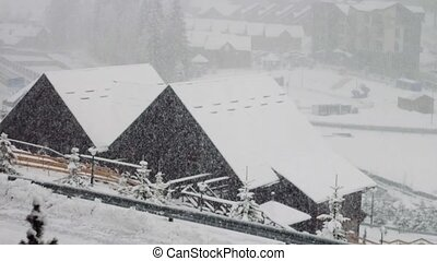 Heavy snowfall on the background of houses and trees