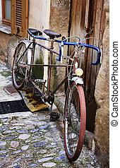 Old bicycle on a medieval street in France