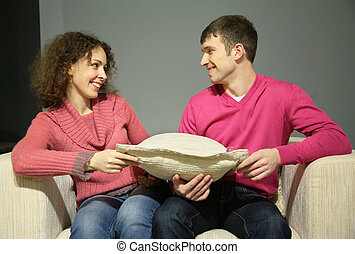 couple sit on sofa with pillow and look at each other