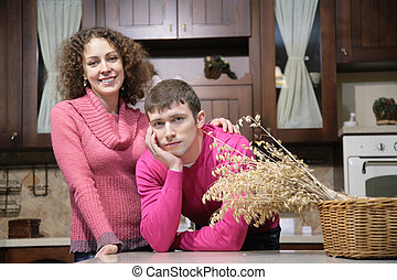 young couple on kitchen and basket with dry herbs