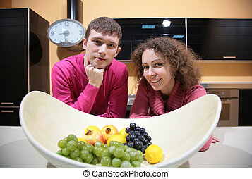 young couple on kitchen and vase with fruits