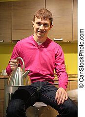 young man in kitchen with steel kettle
