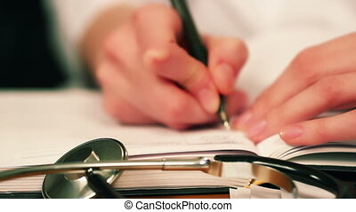 Doctor Writing The Note - Doctor writing the note. Focus on...
