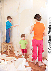 mother with children remove old wallpapers from wall