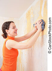 young woman by rag removes  old  wallpapers