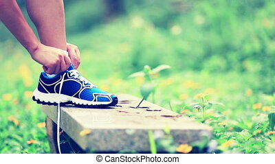 woman runner tying shoelace