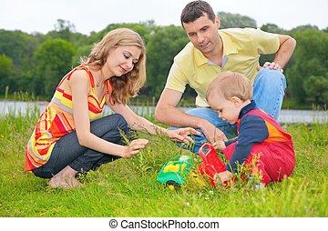 child sits on grass with parents and plays with toy