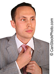 young businessman corrects necktie