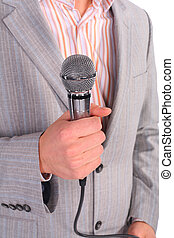 man`s hand holds microphone