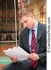 young businessman looks  papers