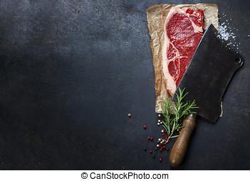vintage cleaver and raw beef steak on dark background