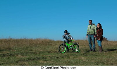 Happy Young Family With a Child On Bike In Autumn Meadow -...
