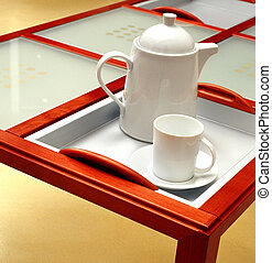 Tea pot and cup on a table