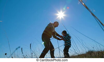 Young Father Spinning His Little Son Around At Nature