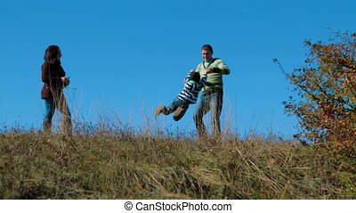 Young Family Walking In Autumn Meadow - Young happy father...