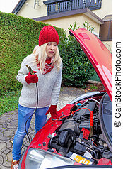 start the vehicle using jumper cables - a young woman takes...