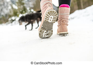 Winter Shoes of a Woman Walking on the Snow