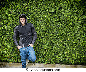 Handsome young man in black hoodie sweater standing outdoor...