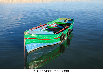 Colorful painted fishing boat moored in blue sea, Syracuse,...