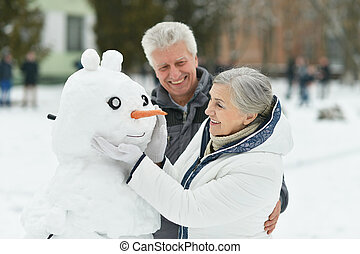 Portrait of elderly couple making snowman and shows thumbs...