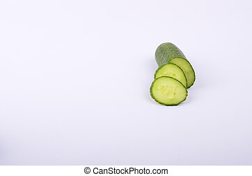 Cucumber slices with a larger peice on white background -...