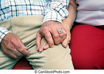hands of a senior couple holding hands with daylight