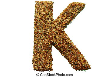 letter k - on a white background from flax seeds lined...