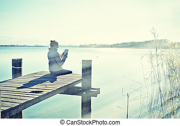 Girl reading from a tablet on the wooden jetty against a...