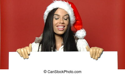 Girl in santa claus hat holding empty board