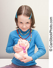 girl child holding a piggy bank